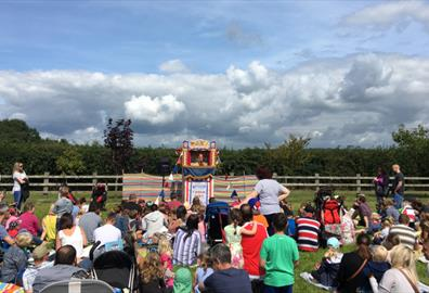 Families enjoy Punch & Judy show at The Donkey Sanctuary Summer Fair